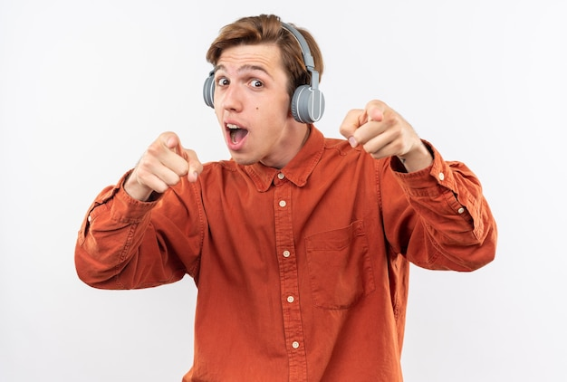 Überraschter junger gutaussehender kerl mit rotem hemd mit kopfhörerpunkten isoliert auf weißer wand