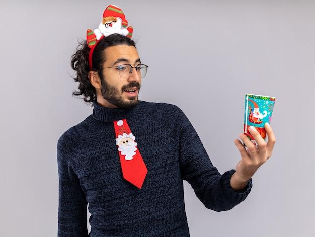 Überraschter junger gutaussehender kerl mit weihnachtskrawatte mit haarreifen, der die weihnachtstasse isoliert auf weißer wand hält und betrachtet