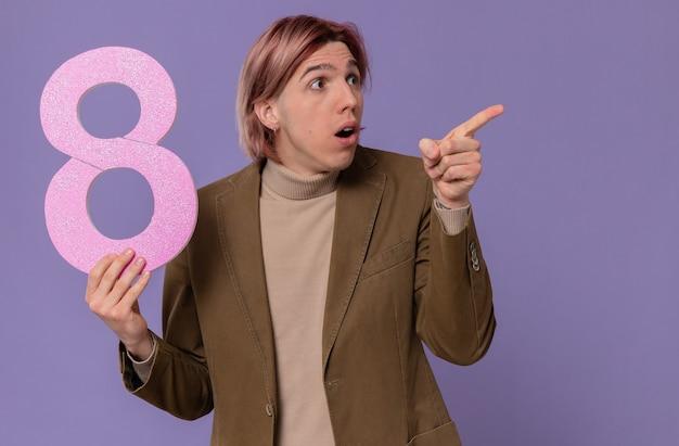 Überraschter junger gutaussehender mann, der rosa nummer acht hält und auf die seite zeigt