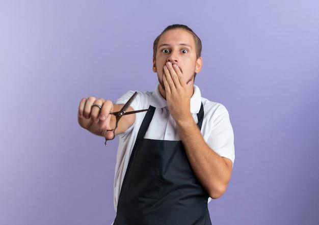 Überraschter junger hübscher friseur, der uniform trägt hand auf mund setzt und schere nach vorne streckt, isoliert auf lila wand