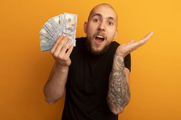 Überraschter junger hübscher kerl, der schwarzes hemd hält, das geld spreizende hand hält