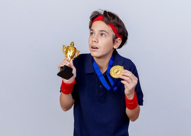 Überraschter junger hübscher sportlicher junge, der stirnband und armbänder mit zahnspangen und medaille um hals hält, der medaille und siegerpokal hält, die seite lokalisiert auf weißer wand betrachten