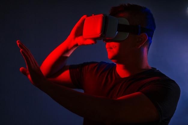 Überraschter junger intelligenter zufälliger mann, der den vr kopfhörer der virtuellen realität gestikuliert hände trägt
