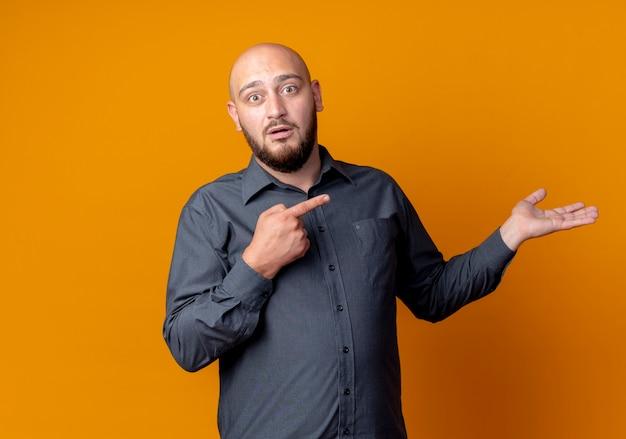 Überraschter junger kahlköpfiger callcenter-mann, der leere hand zeigt und auf sie lokalisiert auf orange wand zeigt