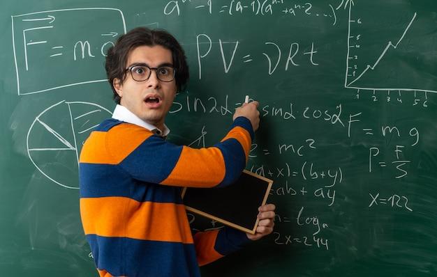 Überraschter junger kaukasischer geometrielehrer, der eine brille trägt, die in der profilansicht vor der tafel im klassenzimmer steht und eine mini-tafel hält, die kreide auf der tafel mit blick auf die seite zeigt