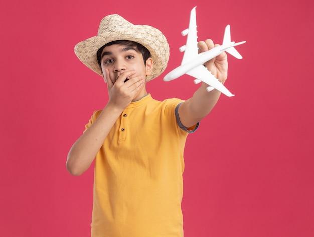Überraschter junger kaukasischer junge mit strandhut, der das modellflugzeug ausstreckt und die hand auf den mund hält