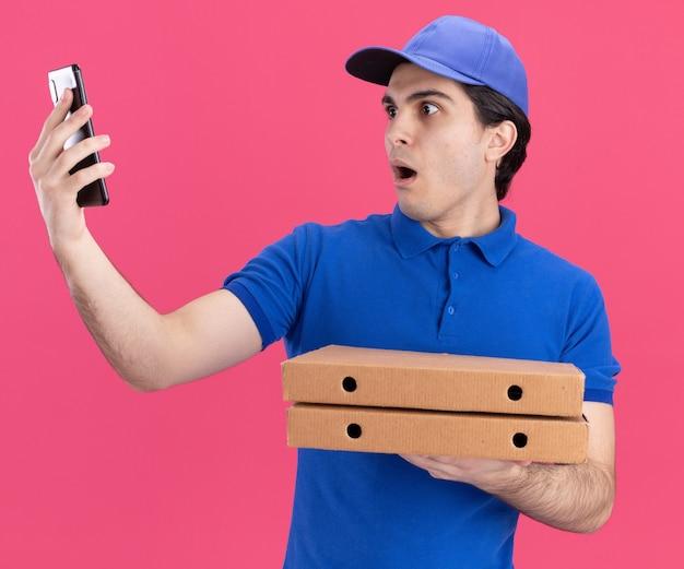 Überraschter junger kaukasischer lieferbote in blauer uniform und mütze mit pizzapaketen, die sich ausstrecken und auf das handy schauen