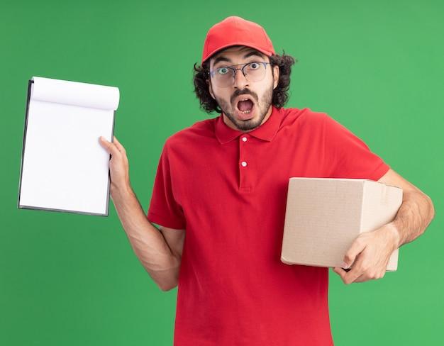 Überraschter junger kaukasischer lieferbote in roter uniform und mütze mit brille, die karton hält und zwischenablage zeigt