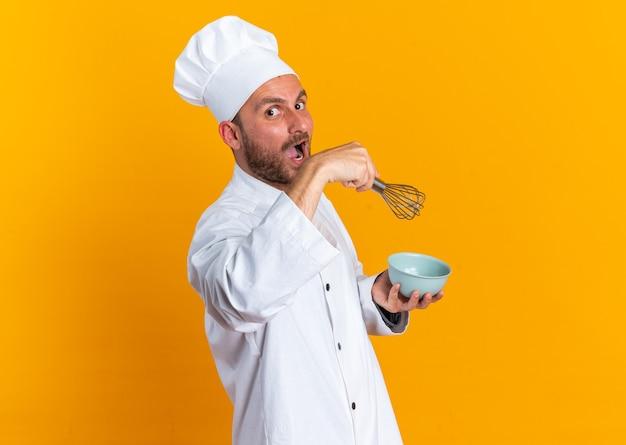 Überraschter junger kaukasischer männlicher koch in kochuniform und mütze, der in der profilansicht mit schüssel und schneebesen steht und die kamera isoliert auf oranger wand mit kopierraum betrachtet