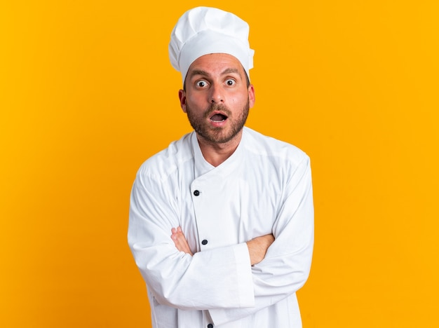 Überraschter junger kaukasischer männlicher koch in kochuniform und mütze, die mit geschlossener haltung steht
