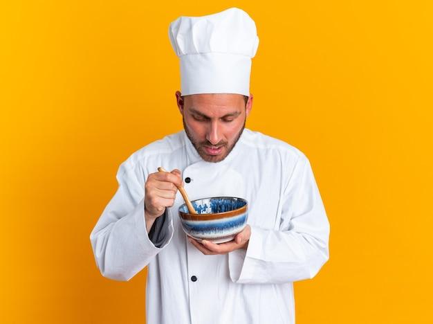 Überraschter junger kaukasischer männlicher koch in kochuniform und mütze mit schüssel und holzlöffel darin, der in die schüssel schaut