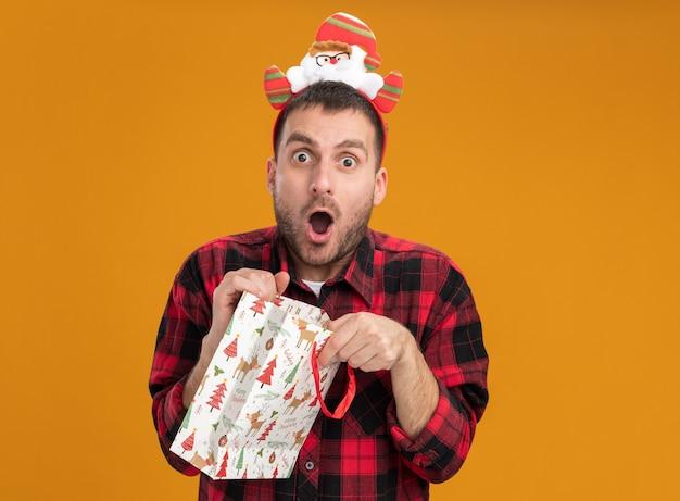 Überraschter junger kaukasischer mann mit weihnachtsmann-stirnband, der eine weihnachtsgeschenktüte hält, die isoliert auf oranger wand mit kopierraum aussieht?