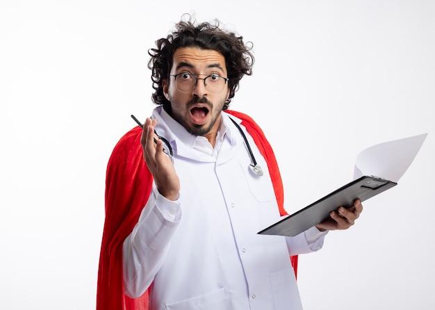 Überraschter junger kaukasischer superheldenmann in der optischen brille, die arztuniform mit rotem umhang und mit stethoskop um hals trägt, hält bleistift und zwischenablage mit kopierraum