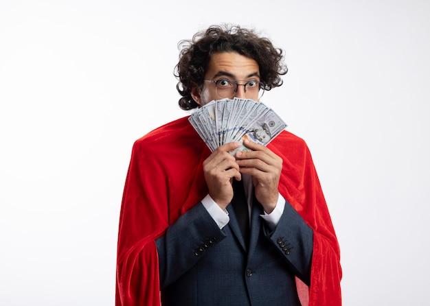 Überraschter junger kaukasischer superheldenmann in optischer brille, der anzug mit rotem mantel trägt, hält geld