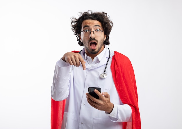 Überraschter junger kaukasischer superheldenmann in optischer brille, der eine arztuniform mit rotem umhang und mit stethoskop um den hals trägt und auf das telefon zeigt