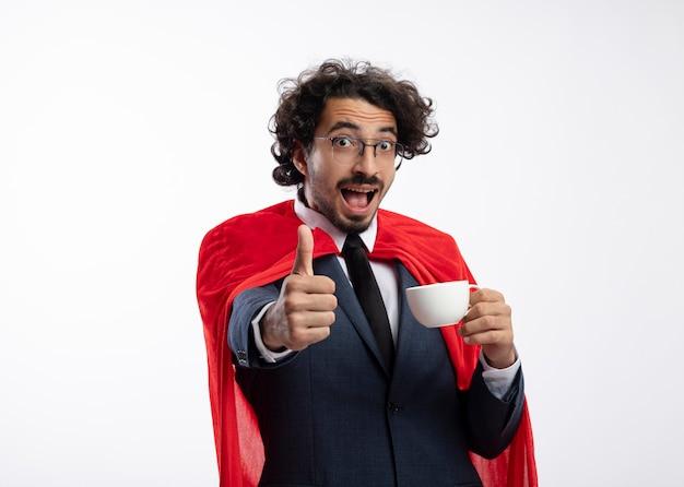 Überraschter junger kaukasischer superheldenmann in optischer brille mit anzug mit rotem umhang, daumen hoch und hält tasse
