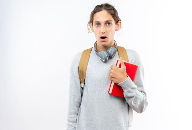 Überraschter junger kerl, der einen rucksack mit kopfhörern am hals trägt und bücher isoliert auf weißer wand hält?