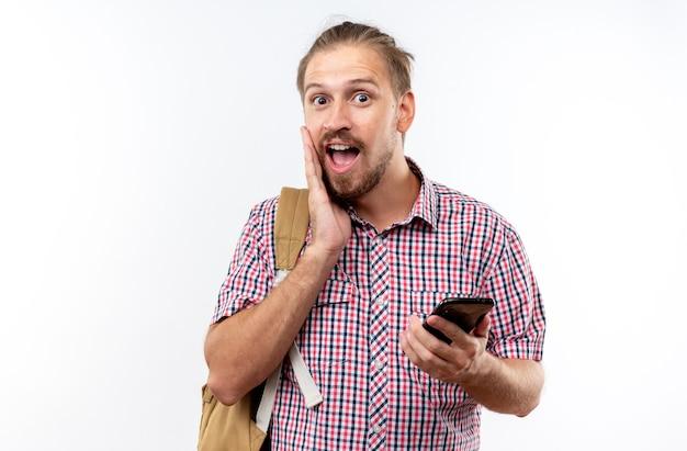 Überraschter junger kerl, der einen rucksack trägt, der das telefon hält und die hand auf die wange legt, isoliert auf weißer wand?