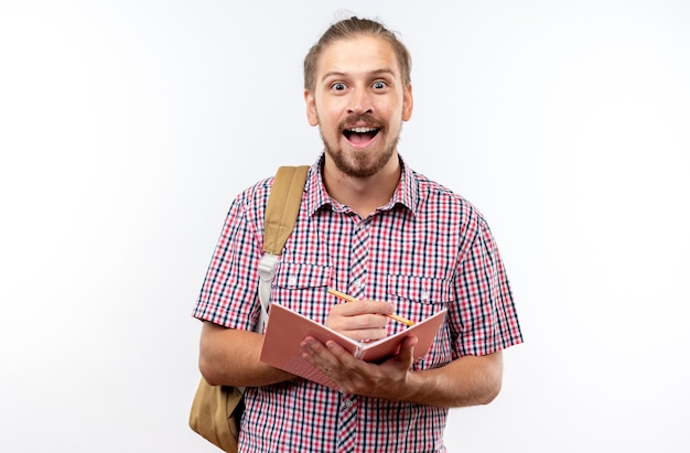 Überraschter junger kerl, der einen rucksack trägt und etwas auf ein notizbuch schreibt, das auf weißer wand isoliert ist?