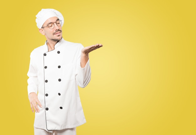 Überraschter junger koch, der etwas mit seiner hand hält
