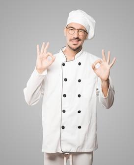 Überraschter junger koch mit einer geste der zustimmung