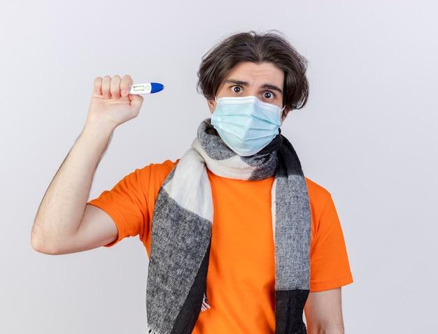 Überraschter junger kranker mann, der schal und medizinische maske hält, die thermometer lokalisiert auf weißem hintergrund hält