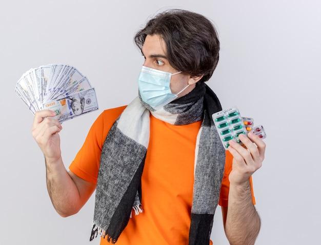 Überraschter junger kranker mann, der schal und medizinische maske trägt, die pillen hält und bargeld in seiner hand lokalisiert auf weiß betrachtet