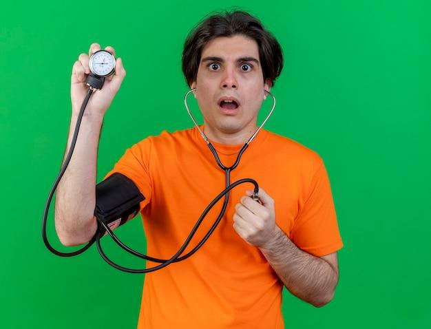 Überraschter junger kranker mann, der seinen eigenen druck mit dem auf grün isolierten blutdruckmessgerät misst