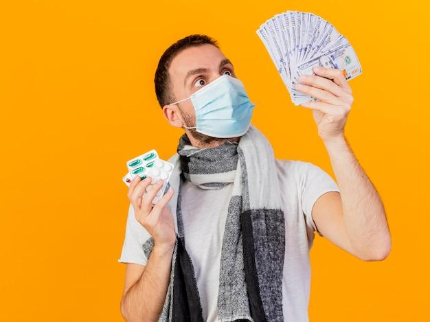 Überraschter junger kranker mann, der wintermütze trägt, die pillen hält und bargeld in seiner hand lokalisiert auf gelbem hintergrund betrachtet
