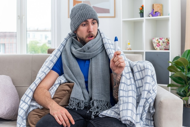 Überraschter junger kranker mann mit schal und wintermütze, der in decke gewickelt auf dem sofa im wohnzimmer sitzt und die hand am bein hält und auf das thermometer schaut