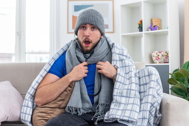 Überraschter junger kranker mann mit schal und wintermütze mit stethoskop, der auf dem sofa im wohnzimmer sitzt und seinen eigenen herzschlag hört