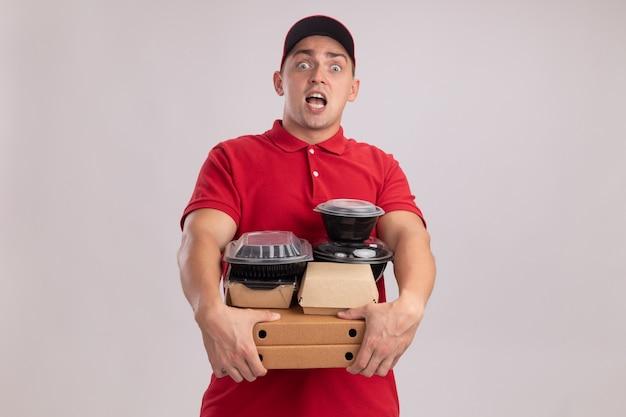 Überraschter junger lieferbote, der uniform mit kappe trägt, die lebensmittelbehälter auf pizzaschachteln lokalisiert auf weißer wand hält