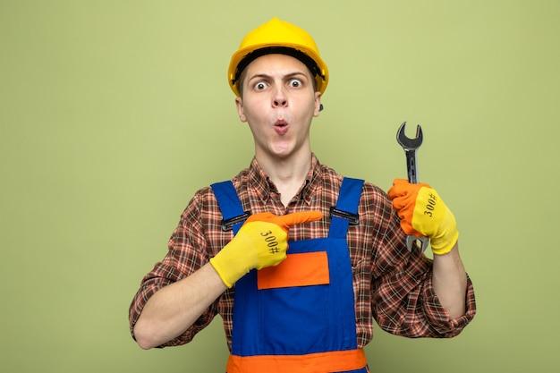 Überraschter junger männlicher baumeister, der eine uniform mit handschuhen trägt und auf einen gabelschlüssel zeigt