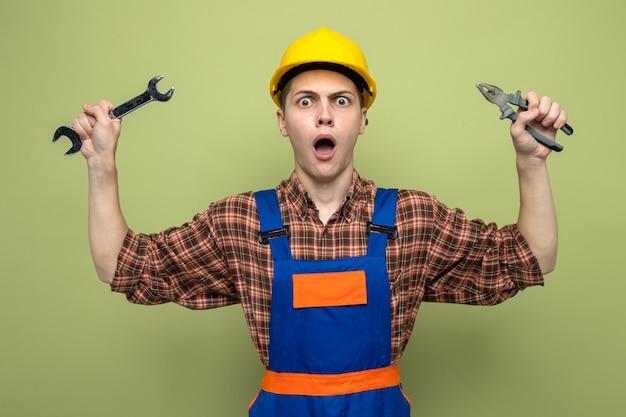 Überraschter junger männlicher baumeister in uniform, der einen gabelschlüssel mit einer zange hält