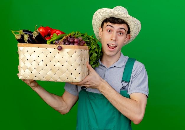 Überraschter junger männlicher gärtner, der gartenhut trägt, hält gemüsekorb