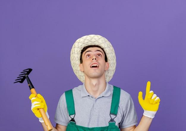 Überraschter junger männlicher gärtner, der gartenhut und handschuhe trägt, hält rechenpunkte mit zwei händen hoch
