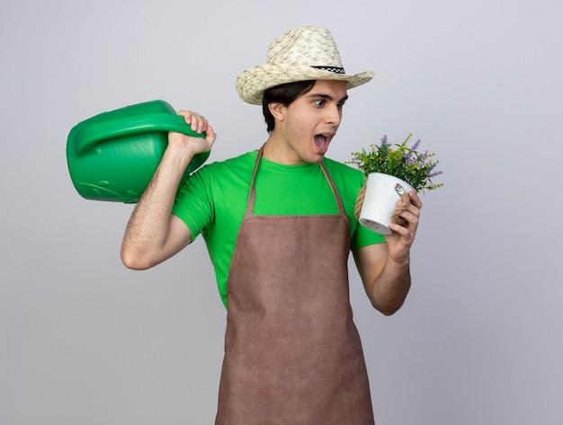 Überraschter junger männlicher gärtner in der uniform, die gartenhut trägt, der bewässerungsdose auf schulter hält und blume im blumentopf in seiner hand betrachtet