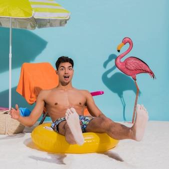 Überraschter junger mann, der auf schwimmenkreis im studio sitzt