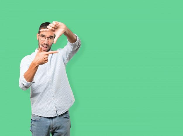 Überraschter junger mann, der eine geste vom machen eines fotos mit den händen macht