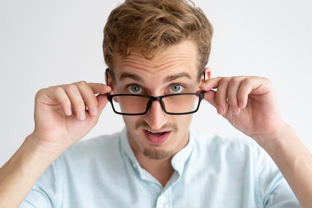 Überraschter junger mann, der kamera über gläsern betrachtet