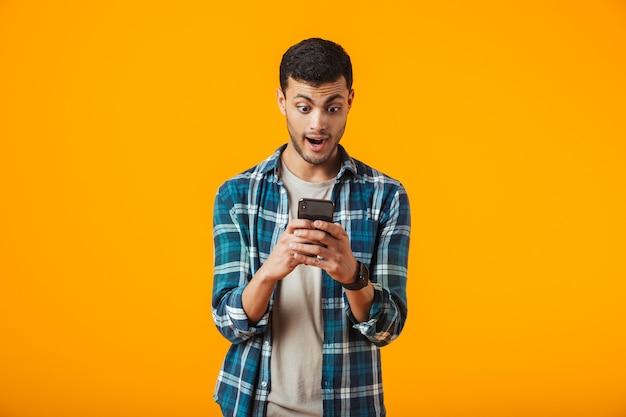 Überraschter junger mann, der kariertes hemd trägt, das lokal über orange wand steht, unter verwendung des handys