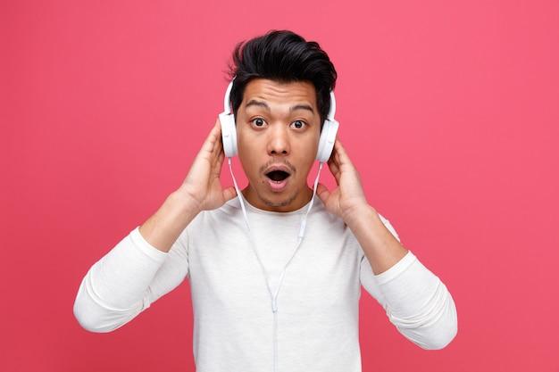 Überraschter junger mann, der kopfhörer trägt, die hände auf ihnen halten, die musik hören
