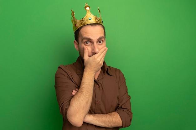 Überraschter junger mann, der krone trägt, die front betrachtet, die hand auf mund lokalisiert auf grüner wand setzt