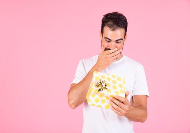 Überraschter junger mann, der offene geschenkbox gegen rosa hintergrund betrachtet