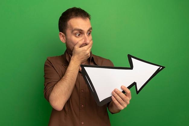 Überraschter junger mann, der pfeilmarkierung hält und betrachtet, die zur seite zeigt, die hand auf mund lokalisiert auf grüner wand hält