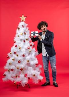 Überraschter junger mann, der sein geschenk hält und tief denkend nahe geschmücktem weißem weihnachtsbaum auf der rechten seite von rot steht