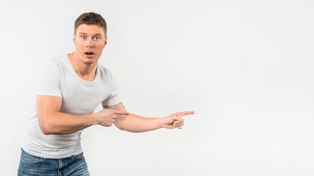 Überraschter junger mann, der seine finger gegen weißen hintergrund zeigt