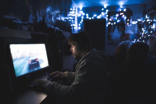 Überraschter junger mann, der spiele am computer spielt.