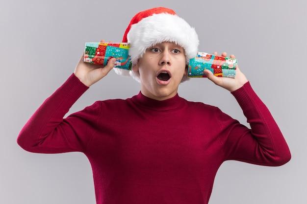 Überraschter junger mann, der weihnachtshut trägt, der weihnachtsbecher auf ohren lokalisiert auf weißem hintergrund hält