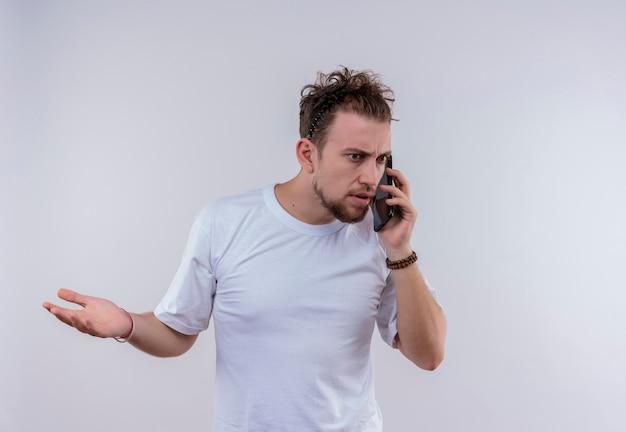 Überraschter junger mann, der weißes t-shirt trägt, spricht am telefon, das hand auf lokalisiertem weißem hintergrund erhebt